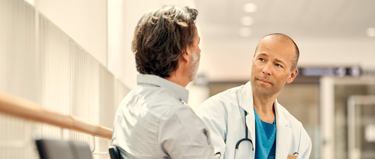 Manlig läkare samtalar med man i sjukhusmiljö.