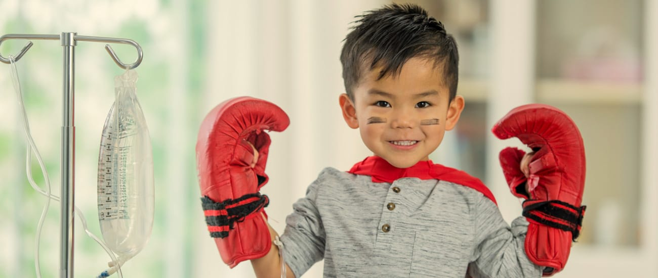 A little boy wearing boxing gloves stands next to a drip stand